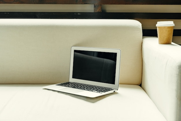 ソファの家のインテリアフリーランサーの職場のコンセプトの近くのテーブルにノートパソコンを開く