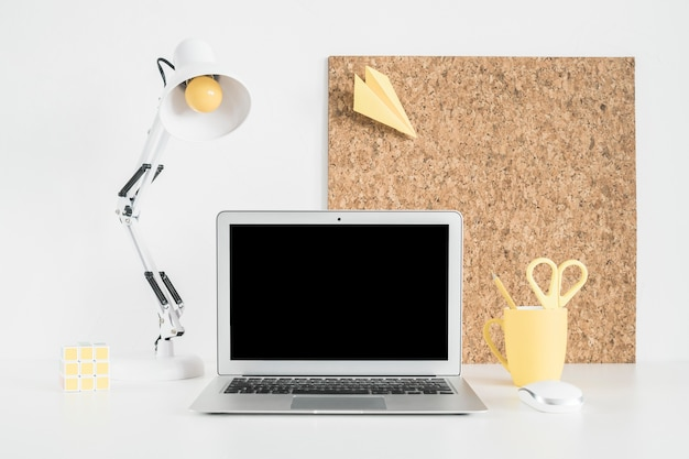 Open laptop on table with airplane on cork board