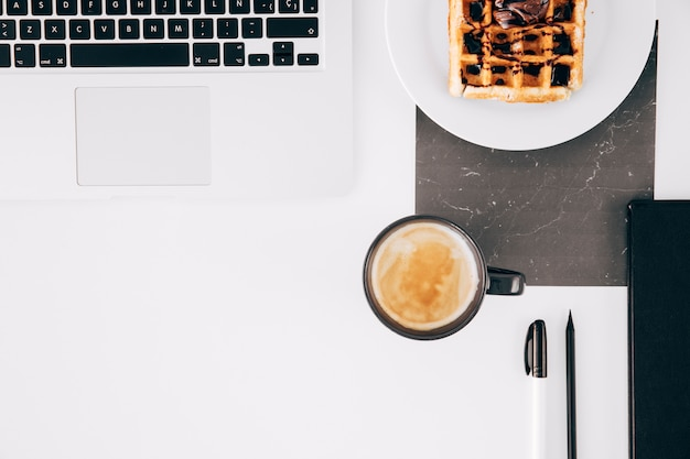 An open laptop; waffle; coffee cup; pencil; pen and open laptop on white desk