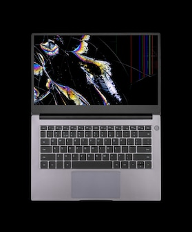 Открытый ноутбук с разбитым экраном в цветных пятнах и трещинах, изолированных на черном фоне, крупным планом, вид сверху