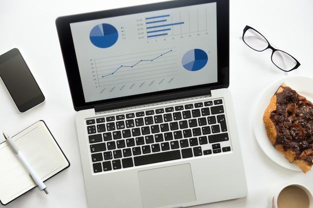 Откройте ноутбук с диаграммой на, очки, мобильный, канцелярские принадлежности