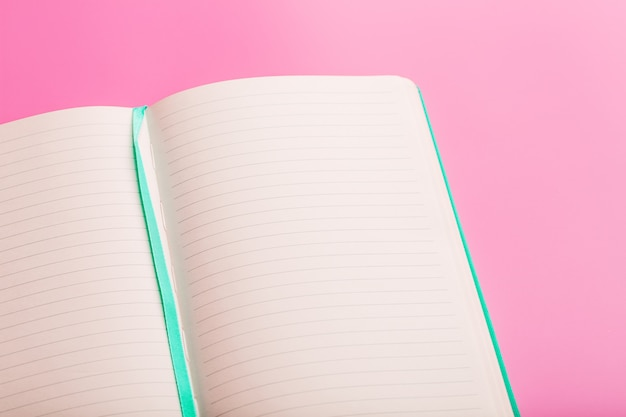 Open a laptop with blank pages on a pink background. top view, copy space