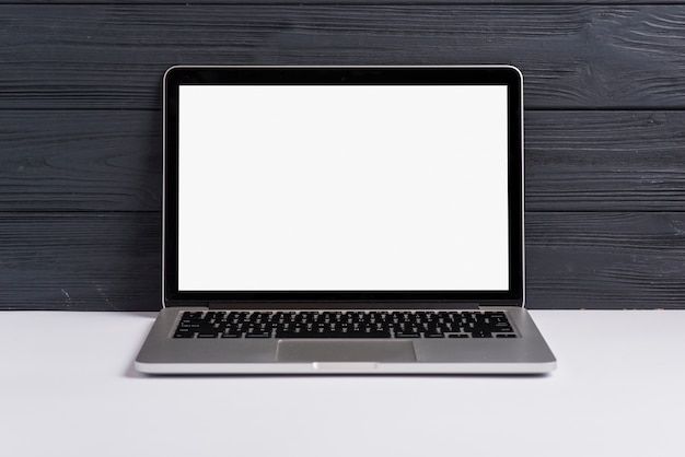 An open laptop with blank white screen on white desk against black wooden backdrop