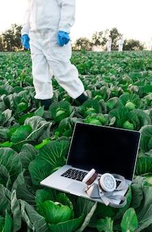 Открытый ноутбук с защитной химической маской лежит на поле