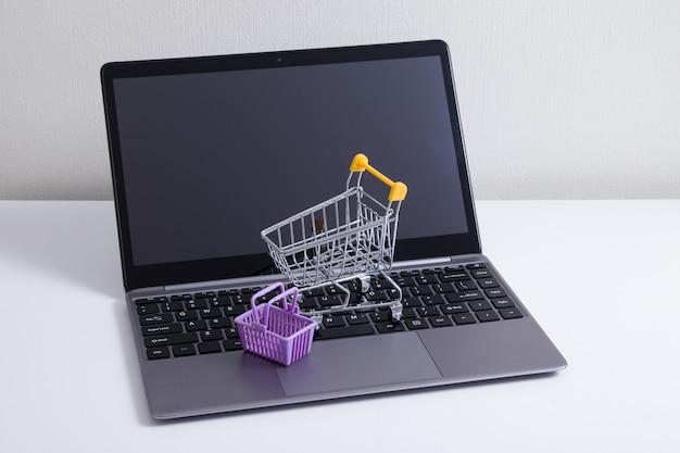 スーパーマーケットのトロリーとバスケットをテーブルに置いたノートパソコンを開く