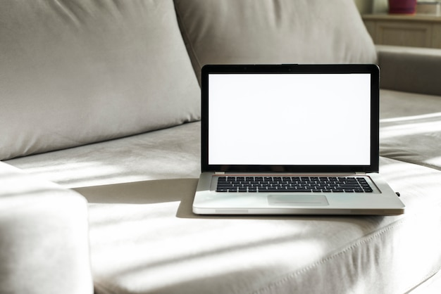 An open laptop with white display screen on gray sofa