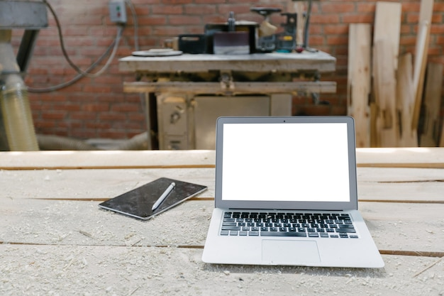 Open laptop in a woodshop with isolated screen