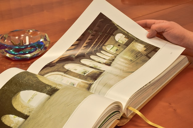 An open large book lies on a brown wooden table, and behind it is an ashtray with several smoked cigars