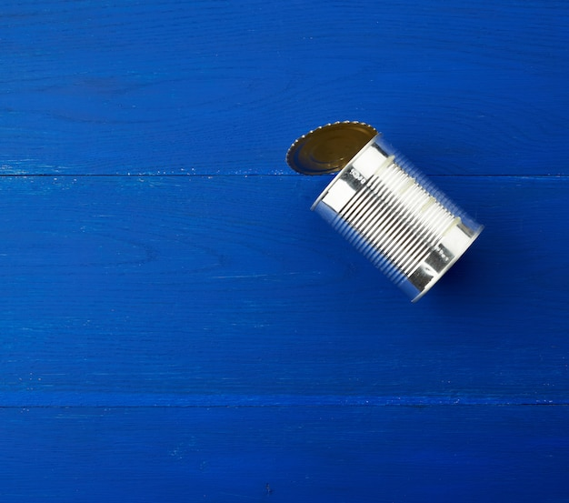 Open large metal tin can on a blue wooden background from parallel boards