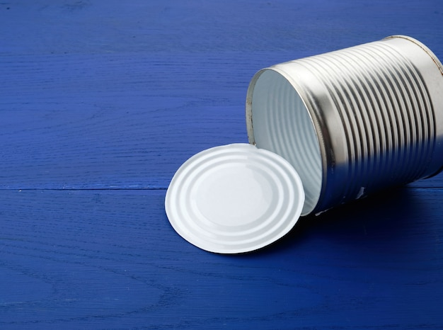 Open large metal tin can on a blue wooden  from parallel boards