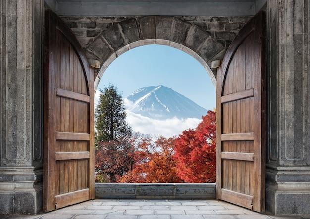 일본의 푸른 하늘에 후지산과 가을 단풍나무가 있는 큰 나무 문을 엽니다.
