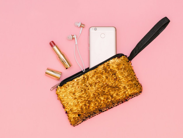 Open lipstick, headphones and phone in a gold-colored bag. pastel color. flat lay.