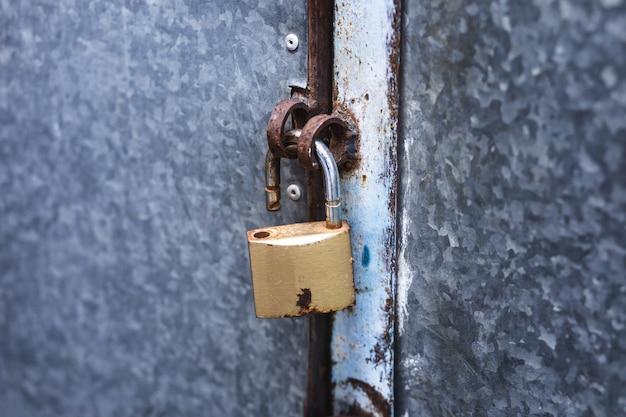 Open lock on a rusty door in the street