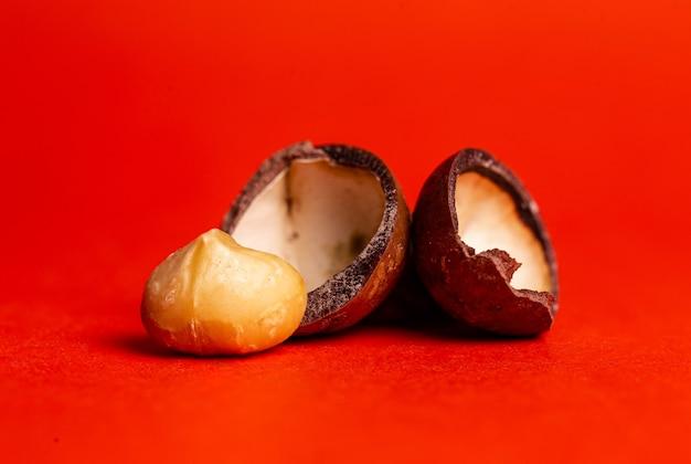 Открыть орех макадамия крупным планом на красном фоне
