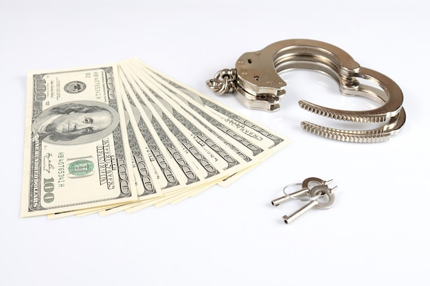 Open metal handcuffs with keys and money