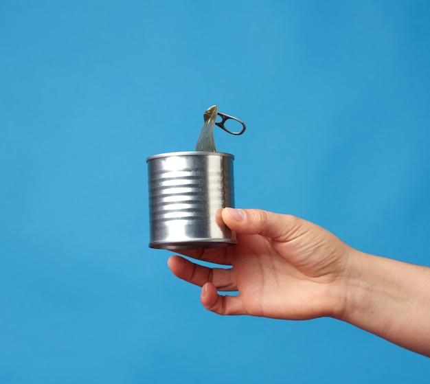青色の背景に女性の手で金属の丸いブリキ缶を開く