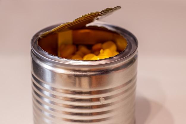 白地にスイートコーンが入った金属製の缶を開けます。