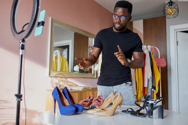 Open-minded afro blogger talk at camera, show new clothes and shoes