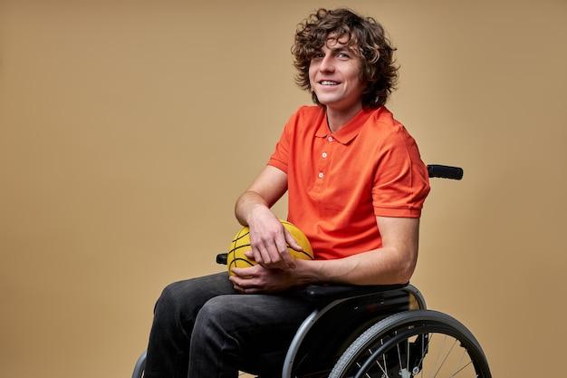 열린 마음을 가진 장애인 남자 농구 공을 들고 웃고, 그는 스포츠 게임을 좋아하고, 더 빨리 발을 내딛는 꿈을 꾸며 포기하지 않습니다.