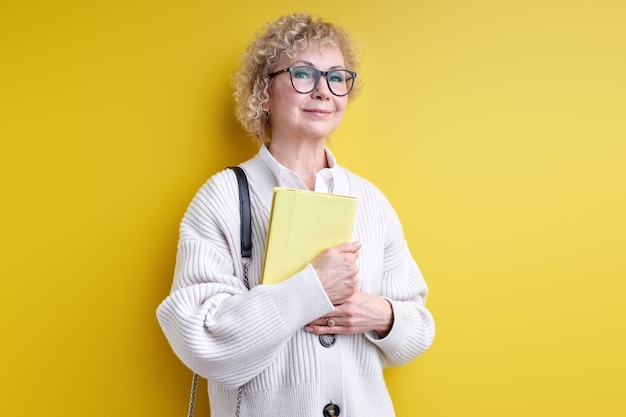 Open-minded senior woman holding book in hands, wearing eyeglasses, confident teacher ready to teach you, experienced tutor posing isolated on yellow
