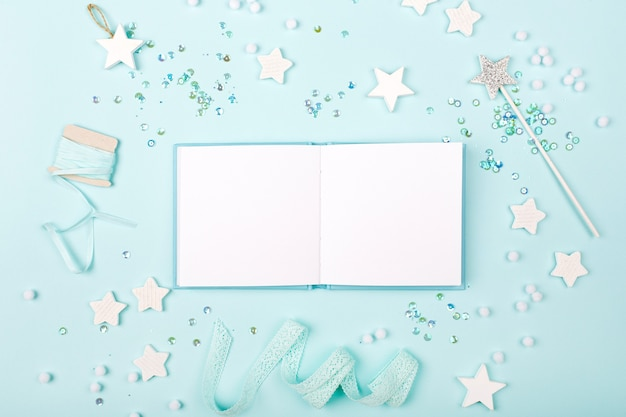 スタイリッシュな装飾の星とスパンコールで青い背景にモックアップミニブックを開きます。赤ちゃんのコンセプト。フラットレイ、上面図