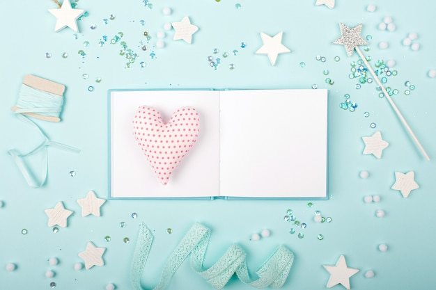 Open mini book mock up with heart on blue background with stylish decoration stars and sequins. baby concept. flat lay, top view
