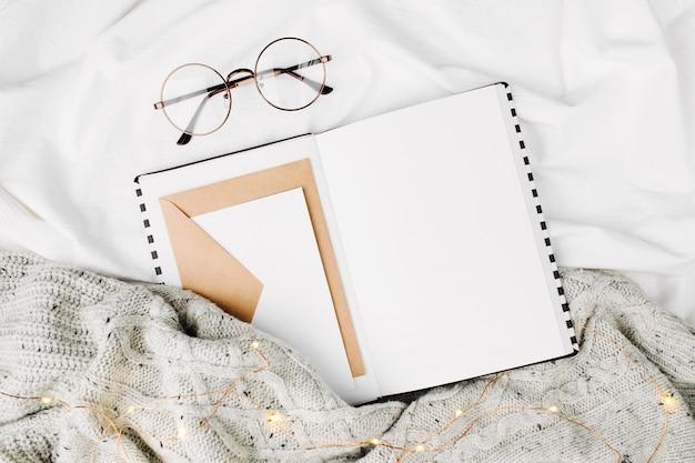 Открытый планировщик мокапов и очки на кровати с теплым пледом. скопируйте пространство. плоская планировка, вид сверху