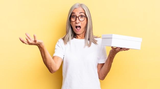口を開けて驚いて、ショックを受けて、信じられないほどの驚きと白い箱を持って驚いた
