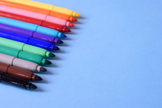 Откройте разноцветные маркеры крупным планом на синем фоне. концепция обратно в школу. место для текста.