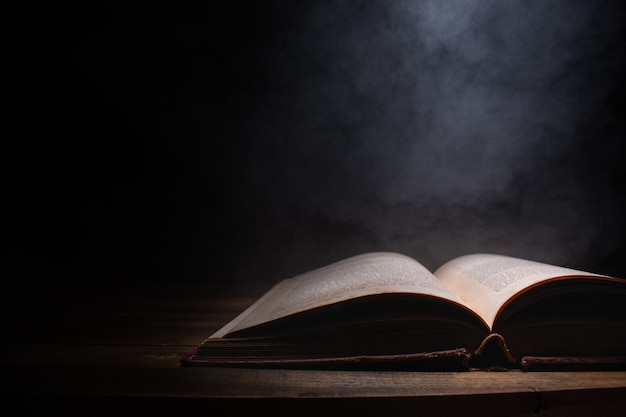 Open a mysterious old book on wooden table, smoke float up from book