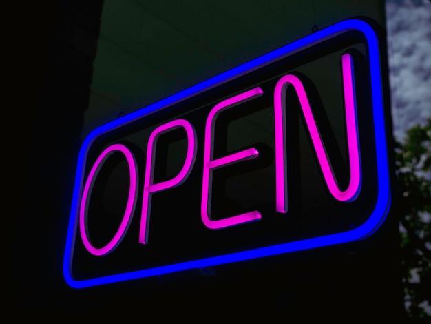 バーやカフェの入り口にあるガラスのopenネオンサイン、暗い背景、ビジネスサイン用の「open」と書かれた青い四角いサインのピンクのテキストが照らされています。