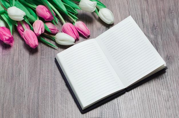 ノートブックを開くと木製のテーブルのチューリップの花を春