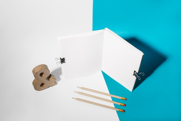Open notebook attach with bulldog clips; pencils and ampersand symbol
