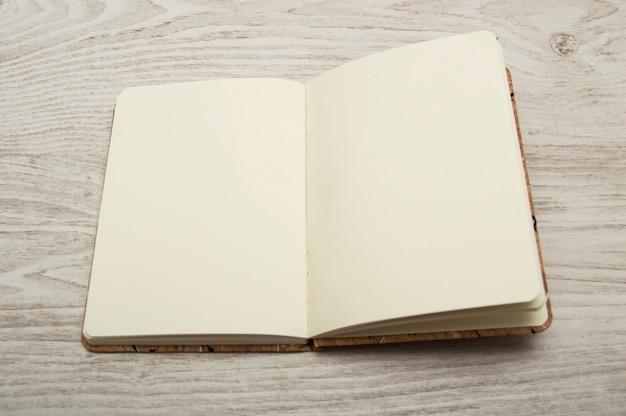Open notebook, blank, on wooden desk.