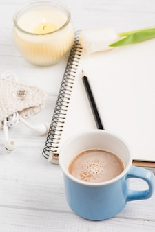 Open notebook, coffe, candle, earpods and tulip