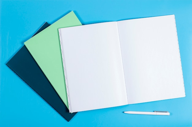 Open notebook and colorful notebooks on blue table. top view