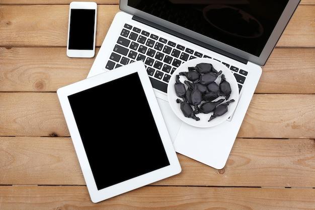 木製のキャンディーの受け皿とノートブック、デジタルタブレット、スマートフォンを開く