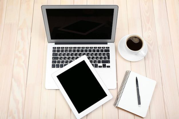 Открытый блокнот, цифровой планшет, дневник и чашка кофе на деревянном