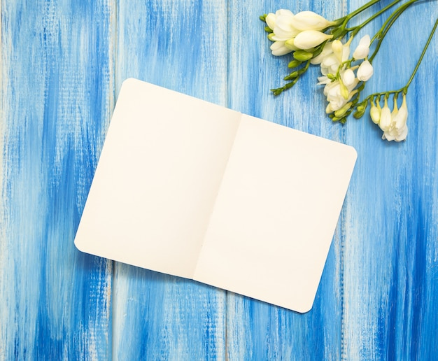 Open notebook and freesia flower on wooden blue background