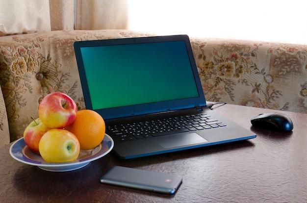 노트북, 과일 접시, 아늑한 주방의 테이블에 스마트 폰을 엽니 다. 단절