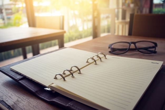 Open notebook and glasses on wooden background