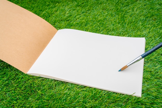 Open notebook on the grass with a pen