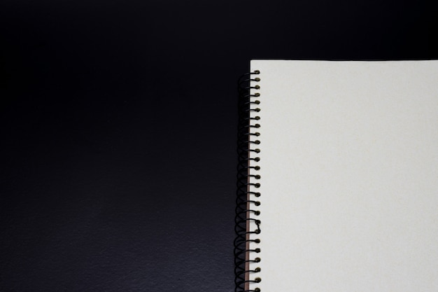 Open notebook half view on a dark rough background with copy space