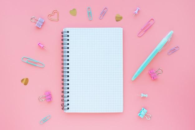 ピンクの背景と周りの文房具の春にボックスでノートブックを開きます。テキストのためのスペース。フラットなレイアウト。