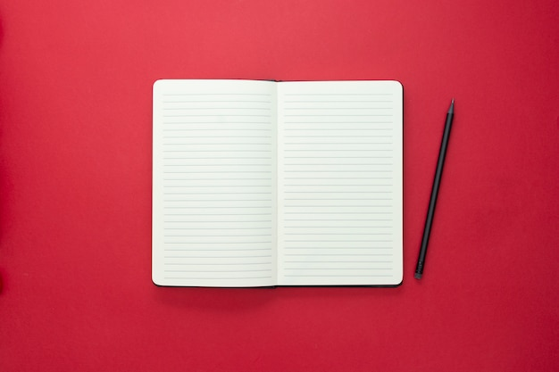 Open notebook isolated on red background, copy space for text.