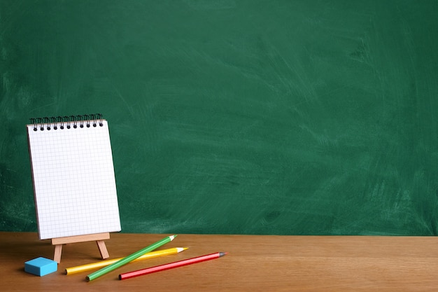 Open notebook on miniature easel and colored pencils on the background of a green chalkboard with chalk stains, copy space