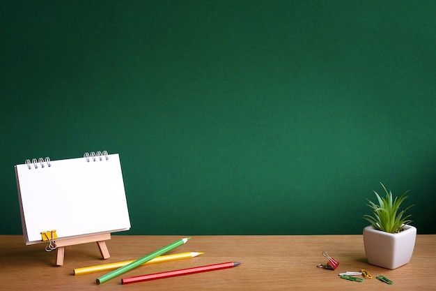 Open notebook on miniature easel, succulent in a pot and colored pencils on the background of a green chalkboard, copy space