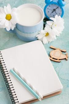 Open notebook, mug of milk