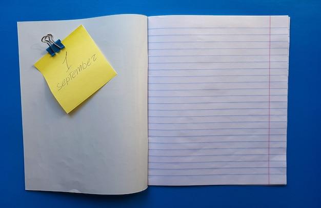 青い木製の卓上に白い裏地でノートブックを開きます。