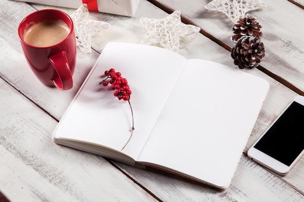 電話とクリスマスの装飾が施された木製のテーブルでノートブックを開きます。